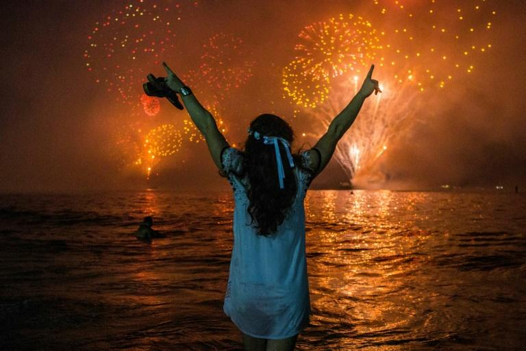 A woman celebrates as she watches the traditional New Year's fireworks at Copacabana Beach in Rio de Janeiro, Brazil with an estimated three million revelers