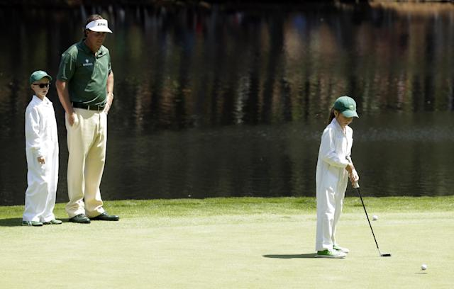 Phil Mickelson watches with his caddie Jim Mackay's son Oliver watches his sister Emma putt during the par three competition at the Masters golf tournament Wednesday, April 9, 2014, in Augusta, Ga. (AP Photo/Chris Carlson)
