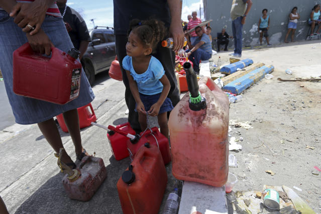 Abi de la Paz de la Cruz, 3, holds a gas can as she waits in line with her family, to get fuel from a gas station, in the aftermath of Hurricane Maria, in San Juan, Puerto Rico, Monday, Sept. 25, 2017. The U.S. ramped up its response Monday to the humanitarian crisis in Puerto Rico while the Trump administration sought to blunt criticism that its response to Hurricane Maria has fallen short of it efforts in Texas and Florida after the recent hurricanes there. (AP Photo/Gerald Herbert)