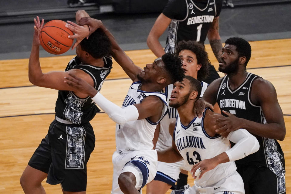 Villanova guard Bryan Antoine, center, stops Georgetown forward Collin Holloway, left, from scoring during the first half of an NCAA college basketball game in the quarterfinals of the Big East conference tournament, Thursday, March 11, 2021, in New York. (AP Photo/Mary Altaffer)