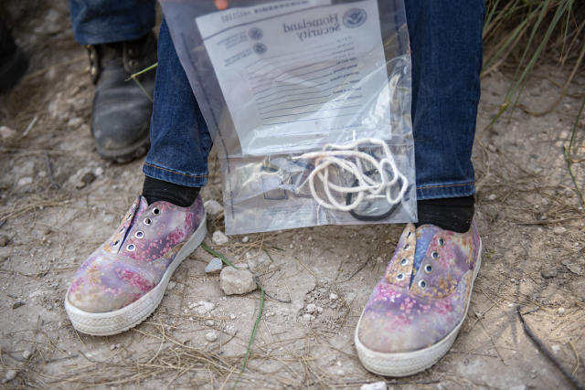 A child holds a bag containing her shoe laces and hair tie. Agents confiscate anything that illegal immigrants may use to hurt themselves or agents after being detained. (Photo: Sergio Flores for Yahoo News)
