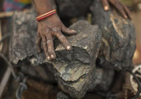 A local woman prepares to carry coal at an open coal field at Dhanbad district in Jharkhand