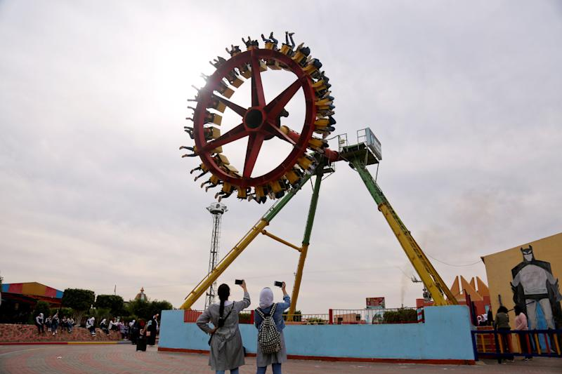 Palestinian schoolgirls take pictures of people enjoying a ride at an amusement park in Gaza City, Nov. 29, 2018. (Photo: Samar Abo Elouf/Reuters)