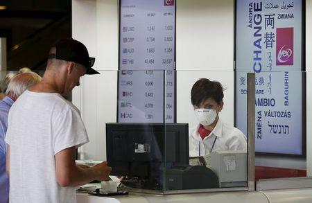 A woman wears a mask as she works at Fiumicino international airport in Rome, Italy, July 13, 2015. REUTERS/Max Rossi