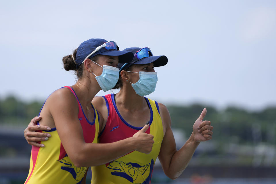 Gold medalists Ancuta Bodnar and Simona Radis of Romania pose for photographers after winning the women's rowing double sculls final at the 2020 Summer Olympics, Wednesday, July 28, 2021, in Tokyo, Japan. (AP Photo/Lee Jin-man)