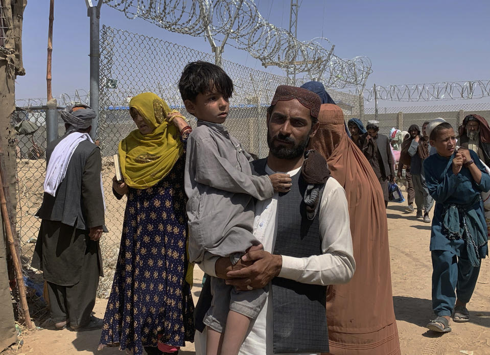 Afghan families cross the border into Pakistan from Afghanistan, in Chaman, Pakistan, Thursday, Aug. 19, 2021. Chaman, is a key border crossing between Pakistan and Afghanistan, normally thousands of Afghans and Pakistanis cross daily and a steady stream of trucks passes through, taking goods to Afghanistan. (AP Photo)