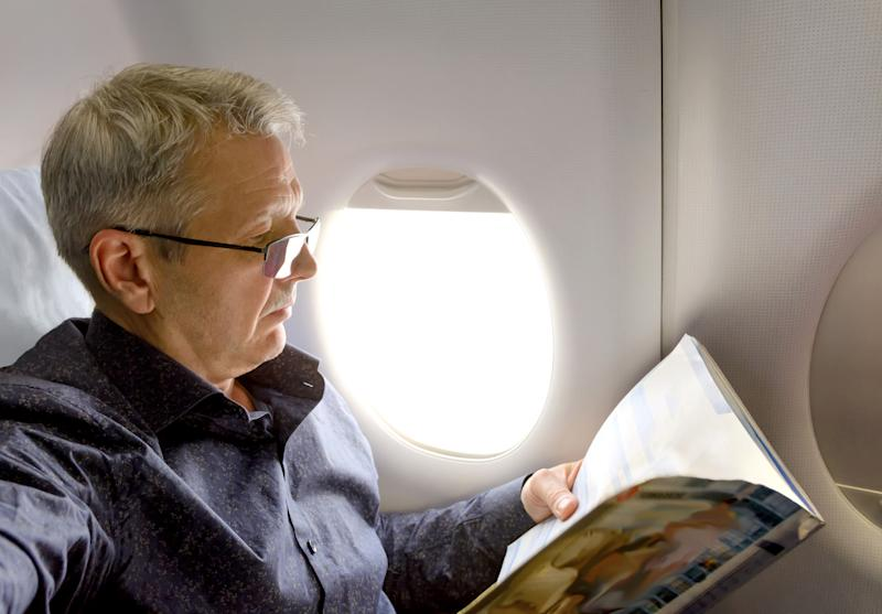 Older man reading a magazine on an airplane