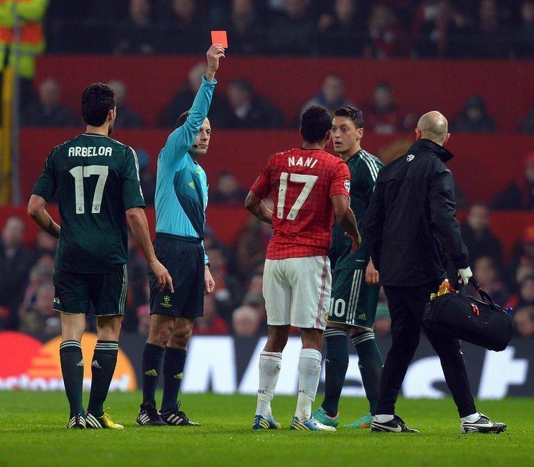 Turkish referee Cuneyt Cakir (2nd L) shows Manchester United's Portuguese midfielder Nani the red card to send him off during the UEFA Champions League round of 16 second leg football match between Manchester United and Real Madrid at Old Trafford in Manchester, northwest England on March 5, 2013. Real Madrid won 2-1 (3-2 on aggregate)
