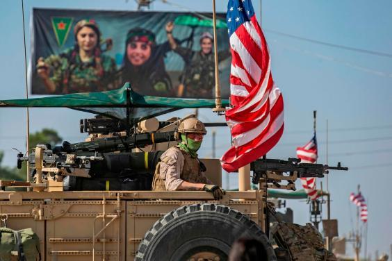 A US armoured vehicle drives past a billboard for the Syrian Kurdish Women's Protection Units (YPJ) (AFP/Getty)
