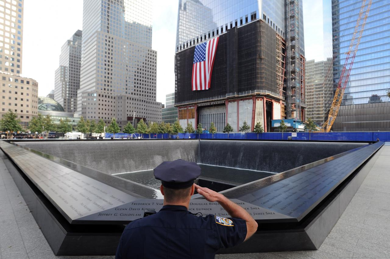 NEW YORK, NY - SEPTEMBER 11:  New York City Police Officer Danny Shea, a military vet, salutes at the North pool of the 9/11 Memorial during the tenth anniversary ceremonies of the September 11, 2001 terrorist attacks at the World Trade Center site, September 11, 2011 in New York City. New York City and the nation are commemorating the tenth anniversary of the terrorist attacks on lower Manhattan which resulted in the deaths of 2,753 people after two hijacked planes crashed into the World Trade Center.  (Photo by David Handschuh-Pool/Getty Images)