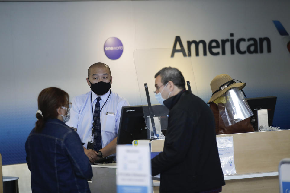 Travelers check in at the American Airlines terminal at the Los Angeles International Airport Thursday, May 28, 2020, in Los Angeles. From Britain's EasyJet to American and Delta in the U.S., airlines are cutting even more jobs to cope with a crushing drop in air travel caused by the coronavirus. (AP Photo/Marcio Jose Sanchez)