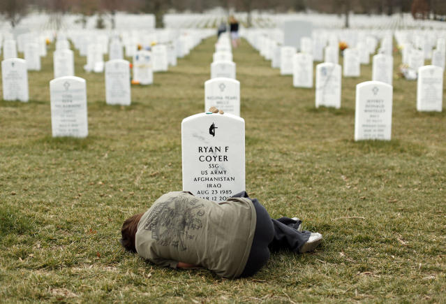 <p>Lesleigh Coyer, 25, of Saginaw, Michigan, lies down in front of the grave of her brother, Ryan Coyer, who served with the U.S. Army in both Iraq and Afghanistan, at Arlington National Cemetery in Virginia, on March 11, 2013. Coyer died of complications from an injury sustained in Afghanistan. (Photo: Kevin Lamarque/Reuters) </p>