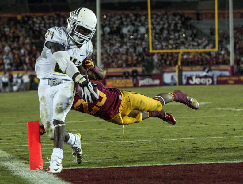Oregon running back Kenjon Barner (24) scores a touchdown as Southern California safety Jawanza Starling (29) attempts to make the stop during the second half of an NCAA college football game, Saturday, Nov. 3, 2012, in Los Angeles. Oregon won 62-51. (AP Photo/Bret Hartman)