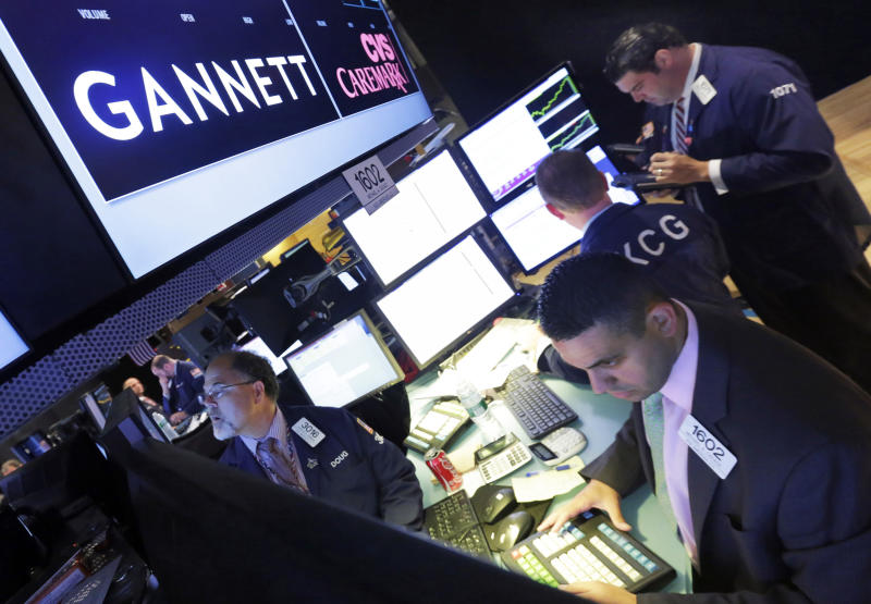 FILE - In this Aug. 5, 2014, file photo, specialist Michael Cacace, foreground right, works at the post that handles Gannett on the floor of the New York Stock Exchange. GateHouse Media closed on its takeover of Gannett Tuesday, Nov. 19, 2019, becoming the country's largest newspaper company by far at a time when print publications are in precipitous decline. (AP Photo/Richard Drew, File)