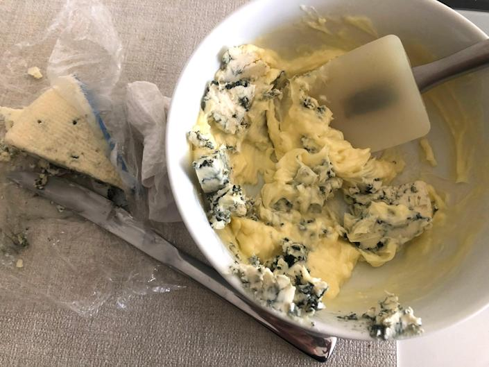 Mixed butter, blue cheese, salt, and pepper in a bowl.