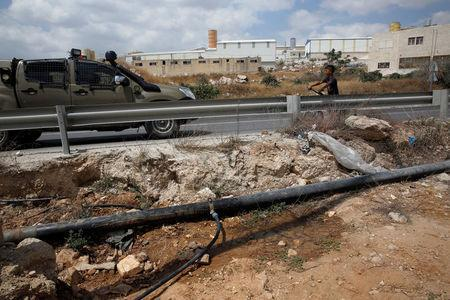 An altered water pipe is seen near a road where a Palestinian boy rides his bicycle near an Israeli Defence Force (IDF) vehicle in the West Bank Jewish settlement of Beit Haggai, near Hebron August 17, 2016. REUTERS/Ronen Zvulun