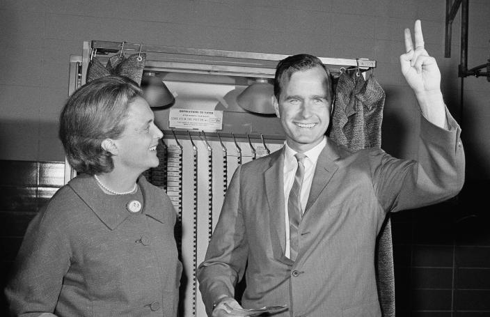 <p>Republican senatorial candidate George Bush shows a victory sign as he and his wife, Barbara, stand in front of a voting machine on Nov. 3, 1964, in Houston, just before casting their ballots. (Photo: Corbis) </p>