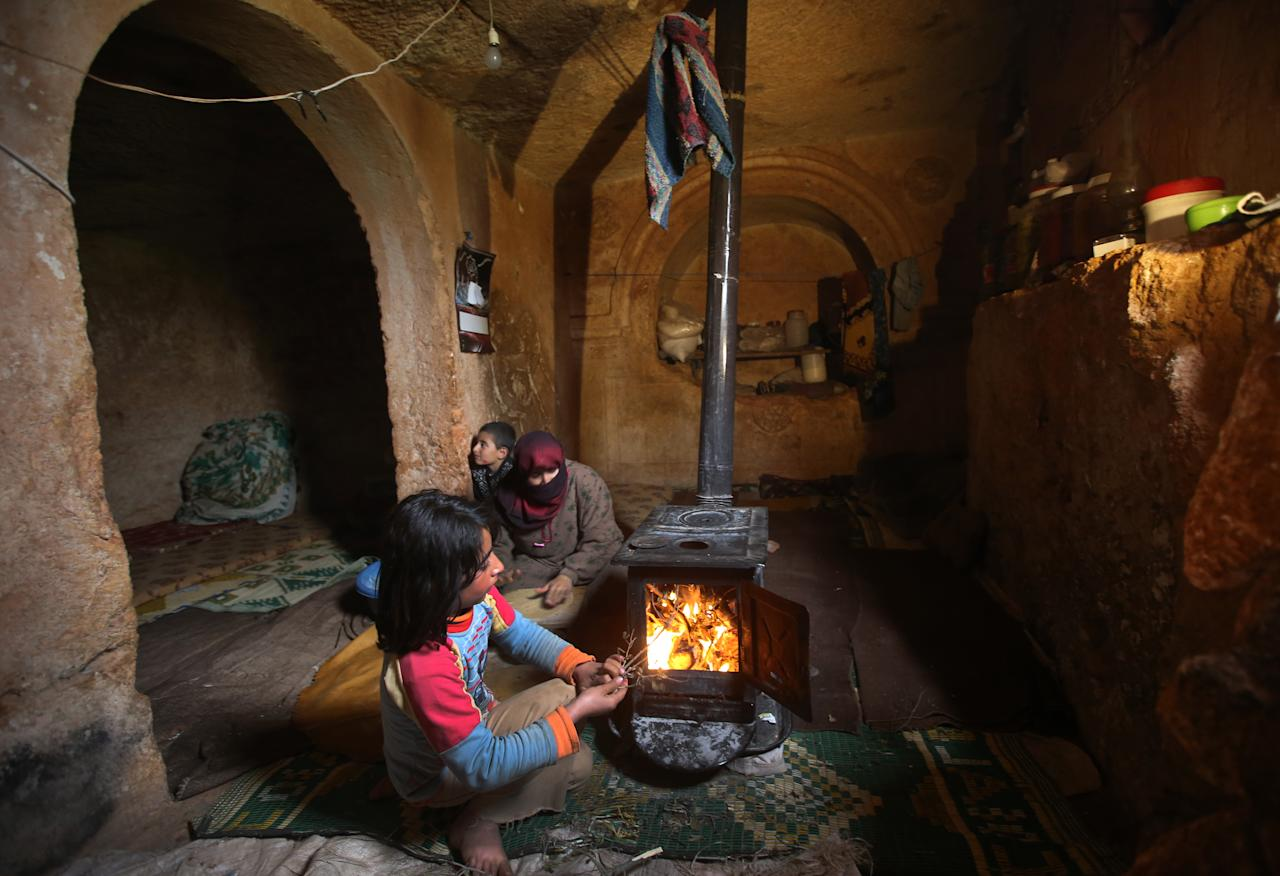 Nihal, 9, puts olive tree branches inside a wooden stove at an underground Roman tomb which they use shelter from Syrian government forces shelling and airstrikes, at Jabal al-Zaweya, in Idlib province, Syria, Thursday Feb. 28, 2013. Across northern Syria, rebels, soldiers, and civilians are making use of the country's wealth of ancient and medieval antiquities to protect themselves from Syria's two-year-old war. They are built of thick stone that has already withstood centuries, and are often located in strategic locations overlooking towns and roads. (AP Photo/Hussein Malla)
