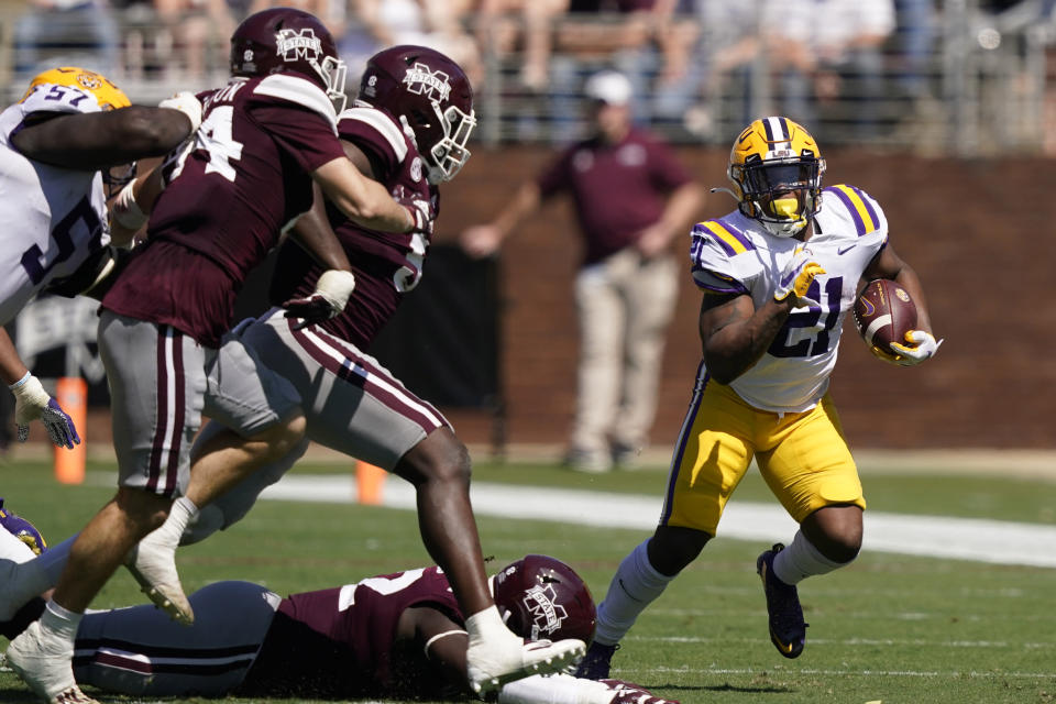 LSU running back Corey Kiner (21) turns the corner for a short gain as Mississippi State players pursue during the first half of an NCAA college football game, Saturday, Sept. 25, 2021, in Starkville, Miss. (AP Photo/Rogelio V. Solis)