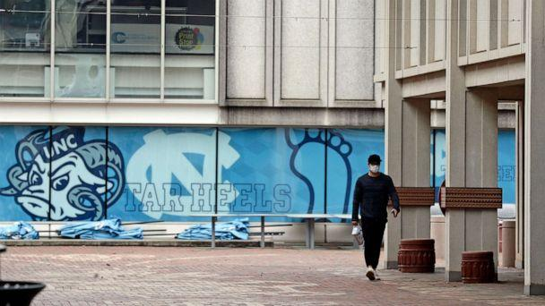 PHOTO: In this March 18, 2020 file photo, a pedestrian walks through campus at the University of North Carolina in Chapel Hill, N.C. (Gerry Broome/AP, File)