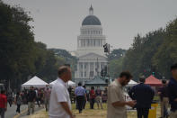 Smoke from area wildfires covers a farmers market and the California Capitol in Sacramento, Calif., Wednesday, July 28, 2021. (AP Photo/Rich Pedroncelli))