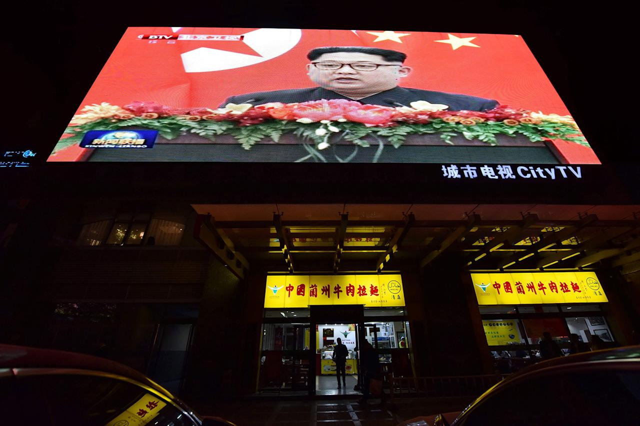 <p>News video footage of North Korean leader Kim Jong Un during his meeting with China's President Xi Jinping is seen on a large screen above a restaurant in Beijing on March 28, 2018. North Korean leader Kim Jong Un was given a lavish welcome by Chinese President Xi Jinping during a secretive trip to Beijing as both sides try to repair frayed relations before Pyongyang's landmark summits with Seoul and Washington. (Photo: Greg Baker/AFP/Getty Images) </p>