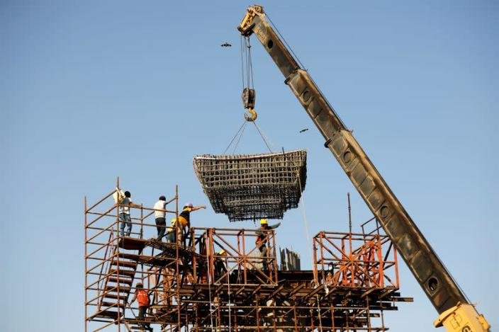 Workers build a pillar at the site of the metro railway flyover under construction in Ahmedabad