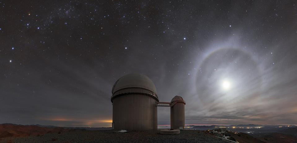 "A lunar ""halo"" lights up the night sky above the 3.6-meter telescope at the La Silla Observatory in Chile. This phenomenon happens when the moon is at an altitude of about 22 degrees above the horizon, where light refracts through icy cirrus clouds. ""Light rays that do this tend to 'bunch up' at the angle that represents the least amount of deviation from their original path. For the particular shape of ice crystal lurking within the cirrus clouds, this minimum deviation angle happens to be around 22 degrees,"" ESO officials said in a description."