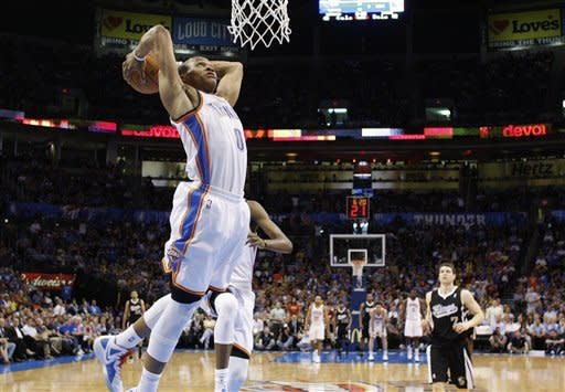Oklahoma City Thunder guard Russell Westbrook goes up for a dunk in front of Sacramento Kings guard Jimmer Fredette (7) during the second quarter of an NBA basketball game in Oklahoma City, Tuesday, April 24, 2012. (AP Photo/Sue Ogrocki)