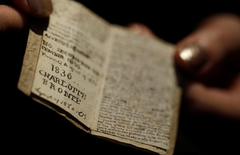 An employee displays the second issue of Young Men's Magazine, a miniature manuscript dated 1830, written by Charlotte Bronte when she was 14 years old, before being put on auction at Drouot auction house in Paris