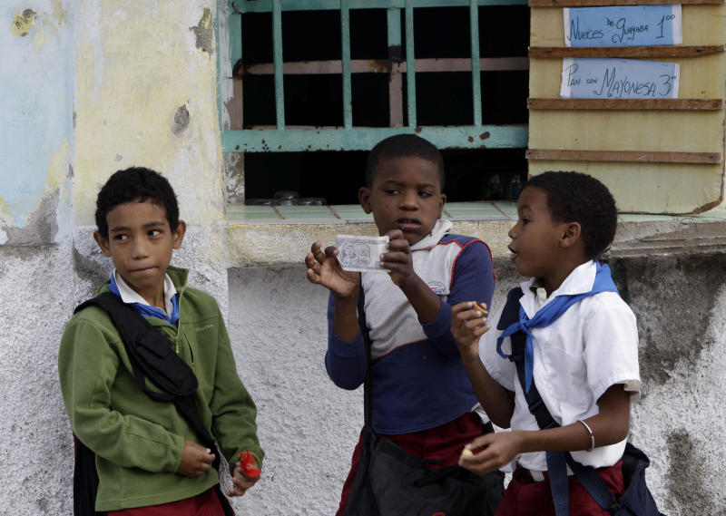 A student shows off a Cuban peso note to his friends before buying a snack in the store behind them as they arrive for school in Havana, Cuba, Tuesday, Nov. 13, 2012. The U.N. General Assembly on Tuesday voted overwhelmingly to condemn the U.S. commercial, economic and financial embargo against Cuba for the 21st year in a row. The embargo was first enacted in 1960 following Cuba's nationalization of properties belonging to U.S. citizens and corporations. (AP Photo/Franklin Reyes)