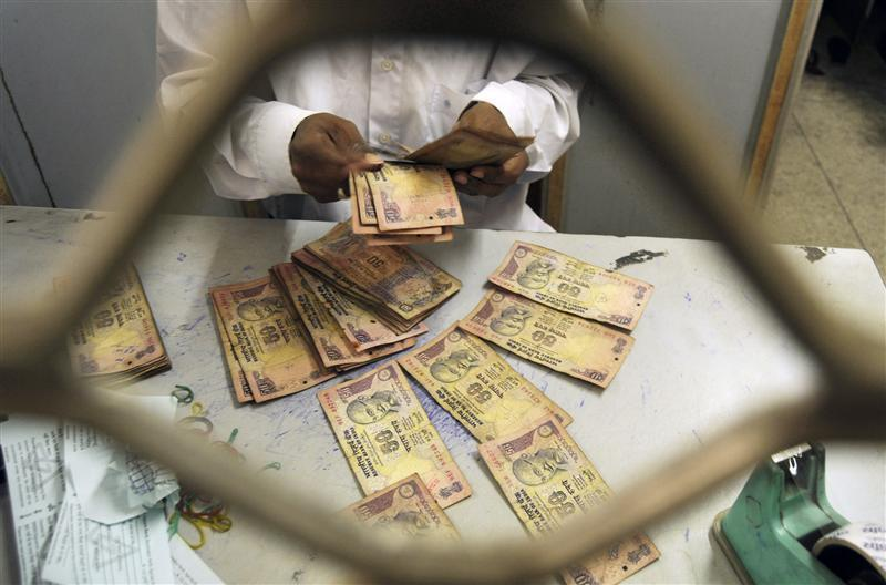 An employee sorts Indian currency notes at a cash counter inside a bank in Agartala