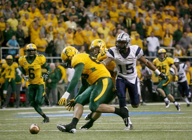 North Dakota State defensive tackle Leevon Perry (69) scoops up the fumble ahead of New Hampshire wide receiver R. J. Harris (15) and scores a touchdown during the first half of an NCAA Football Championship Subdivision semifinal game on Friday, Dec. 20, 2013, at the Fargodome in Fargo, N.D. (AP Photo/Bruce Crummy)