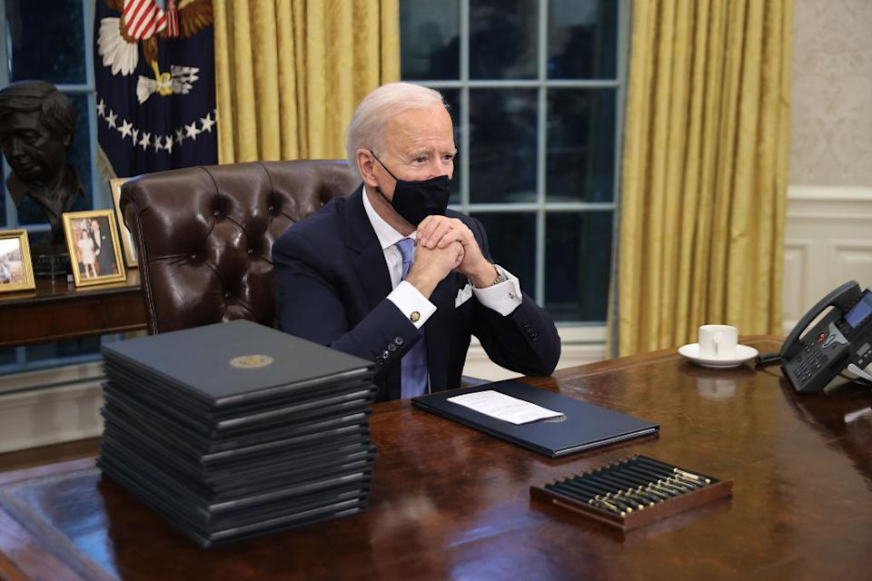 US President Joe Biden prepares to sign a series of executive orders at the Resolute Desk in the Oval Office.