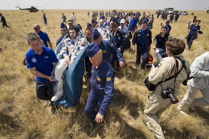 Support and medical personnel carry Expedition 31 Commander Oleg Kononenko of Russia, foreground, and Flight Engineers Andre Kuipers of the European Space Agency, center, and Don Pettit of NASA, background, to the medical tent shortly after they landed in their Soyuz TMA-03M capsule in a remote area near the town of Zhezkazgan, Kazakhstan, on Sunday, July 1, 2012. Pettit, Kononenko and Kuipers returned from more than six months onboard the International Space Station where they served as members of the Expedition 30 and 31 crews. (AP Photo/NASA, Bill Ingalls)