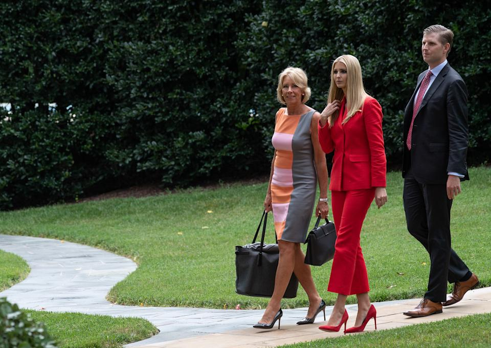 US Education Secretary Betsy DeVos (L), Ivanka Trump (C) and Eric Trump walk to board Marine One at the White House in Washington, DC, on July 31, 2018 as US President Donald Trump departs for Florida. (Photo by NICHOLAS KAMM / AFP)        (Photo credit should read NICHOLAS KAMM/AFP via Getty Images)