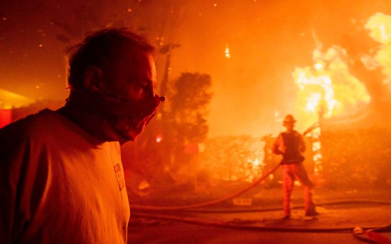 A man walks past a burning home during the Getty fire, in Los Angeles, California on October 28, 2019. | Christian Monterrosa/AP/Shutters/Getty Images