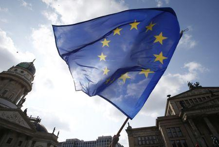 """Participant of the Pro-Europe """"Pulse of Europe"""" movement waves European Union flag during a protest at Gendarmenmarkt square in Berlin"""
