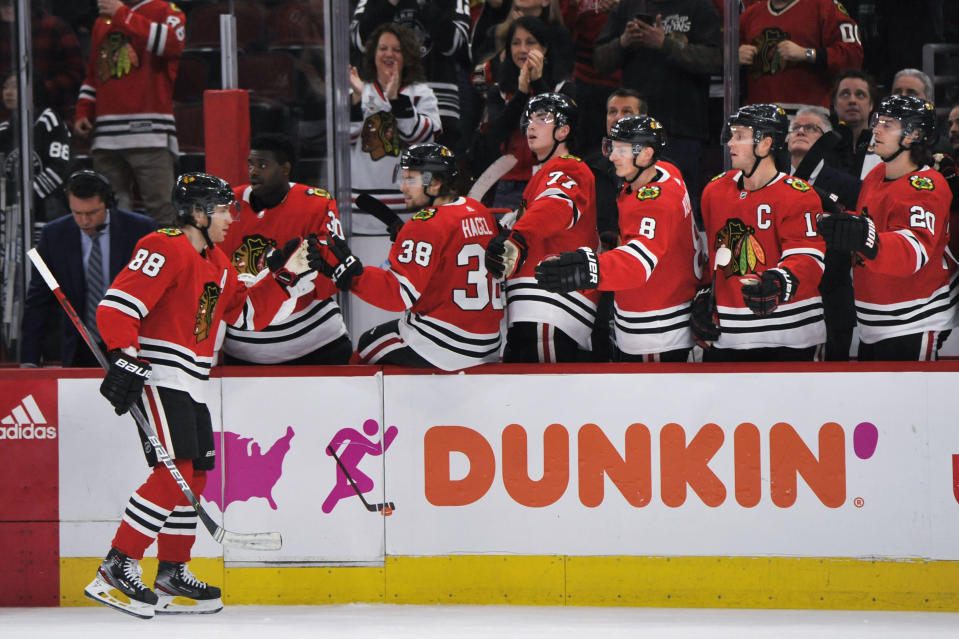 Chicago Blackhawks' Patrick Kane (88) celebrates with teammates on the bench after scoring a goal during the third period of an NHL hockey game against the San Jose Sharks on Wednesday, March 11, 2020, in Chicago. Chicago won 6-2. (AP Photo/Paul Beaty)