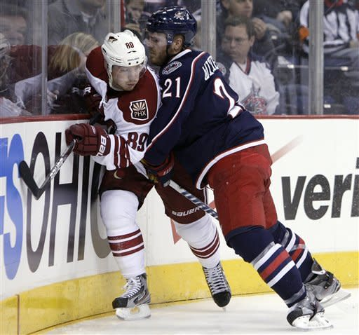 Columbus Blue Jackets' James Wisniewski, right, checks Phoenix Coyotes' Mikkel Boedker, of Denmark, during the during the first period of an NHL hockey game Tuesday, March 6, 2012, in Columbus, Ohio. (AP Photo/Jay LaPrete)