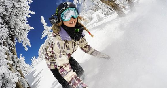 Woman snowboarding while using a GoPro camera