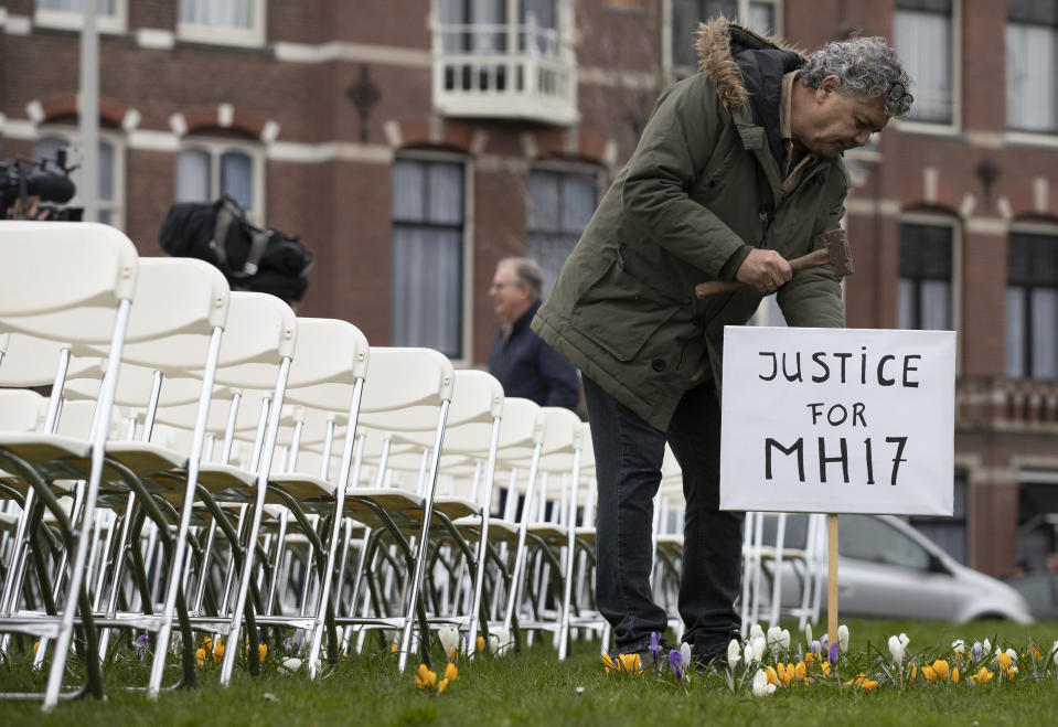 FILE- In this Sunday, March 8, 2020, file photo Rob Fredriksz, who lost his son Bryce and his girlfriend Daisy, places a sign next to 298 empty chairs, each chair for one of the 298 victims of the downed Malaysia Air flight MH17, in a park opposite the Russian embassy in The Hague, Netherlands. The trial in absentia in a Dutch courtroom of three Russians and a Ukrainian charged in the downing of Malaysia Airlines flight MH17 in 2014 moves to the merits phase, when judges and lawyers begin assessing evidence. (AP Photo/Peter Dejong, File)