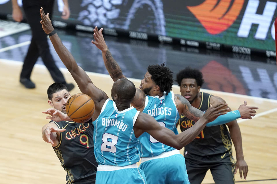 Charlotte Hornets' Bismack Biyombo (8) and Miles Bridges (0) pressure Chicago Bulls' Nikola Vucevic (9) who passes the ball during the first half of an NBA basketball game Thursday, April 22, 2021, in Chicago. (AP Photo/Charles Rex Arbogast)