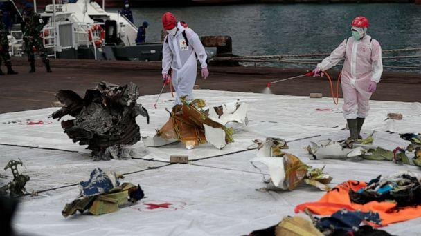 PHOTO: Workers spray disinfectant at parts of aircraft recovered from Java Sea where a Sriwijaya Air passenger jet crashed, at Tanjung Priok Port in Jakarta, Indonesia, Jan. 11, 2021. (Dita Alangkara/AP)