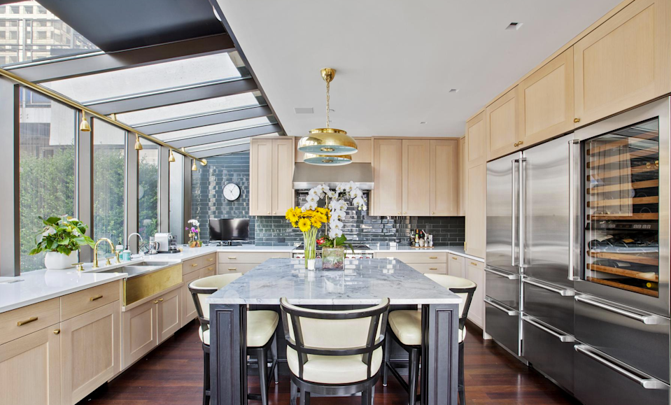 <p>The chef's kitchen features top-of-the-line appliances, a custom wine fridge and a white marble island. The kitchen also opens up to a private outdoor seating and entertainment area. (Douglas Elliman) </p>
