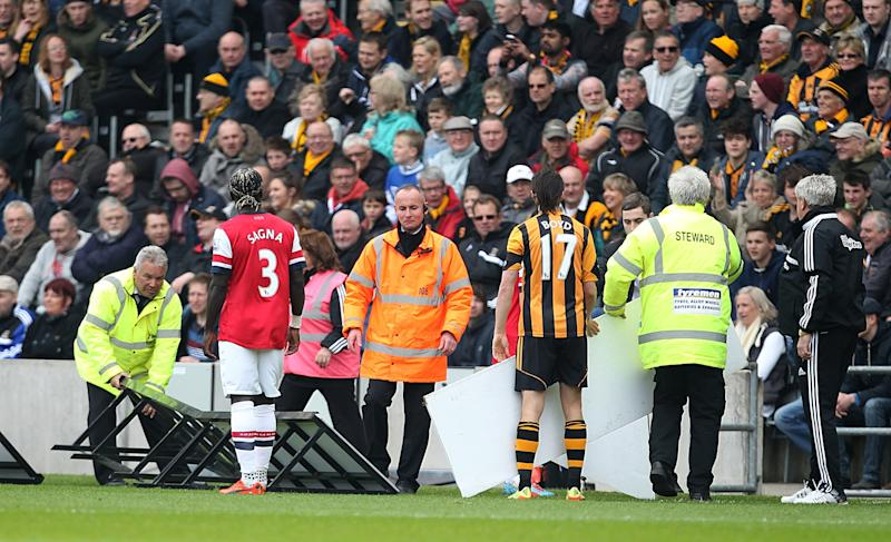 Players and stewards help replace the advertising boards after they were blown onto the pitch during the English Premier League match Hull City against Arsenal at The KC Stadium, Hull, England, Sunday April 20, 2014. (AP Photo/PA, Lynne Cameron) UNITED KINGDOM OUT NO SALES NO ARCHIVE