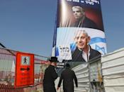 Ultra-Orthodox Jews walk past an election campaign poster bearing the image of opposition leader Yair Lapid (top) and Prime Minister Benjamin Netanyahu (bottom), in the central Israeli city of Bnei Brak