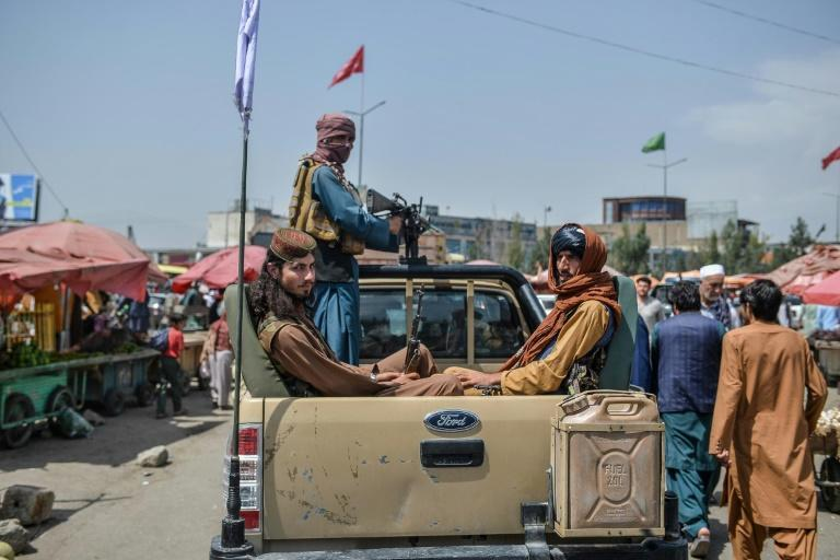 Taliban fighters patrol aboard a pick-up truck in Kabul after they seized control of the Afghan capital