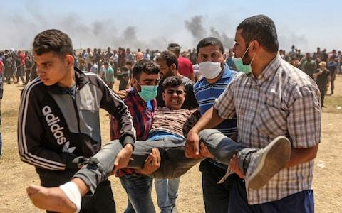 Palestinians carry an injured protester  - Credit:  MAHMUD HAMS/AFP