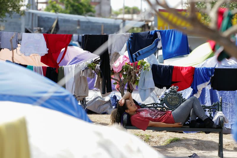 An asylum-seeking migrant, who was apprehended and returned to Mexico under Title 42 after crossing the border from Mexico into the U.S., rests in a public square where hundreds of migrants live in tents, in Reynosa